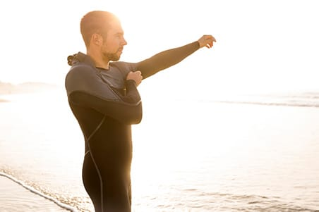 man putting on wetsuit